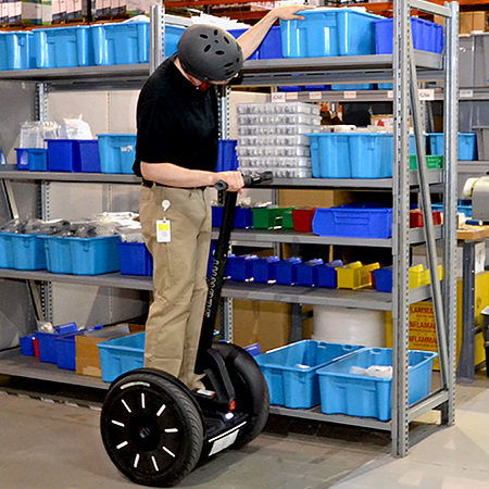Warehouse worker reaching up on shelves while on Segway PT