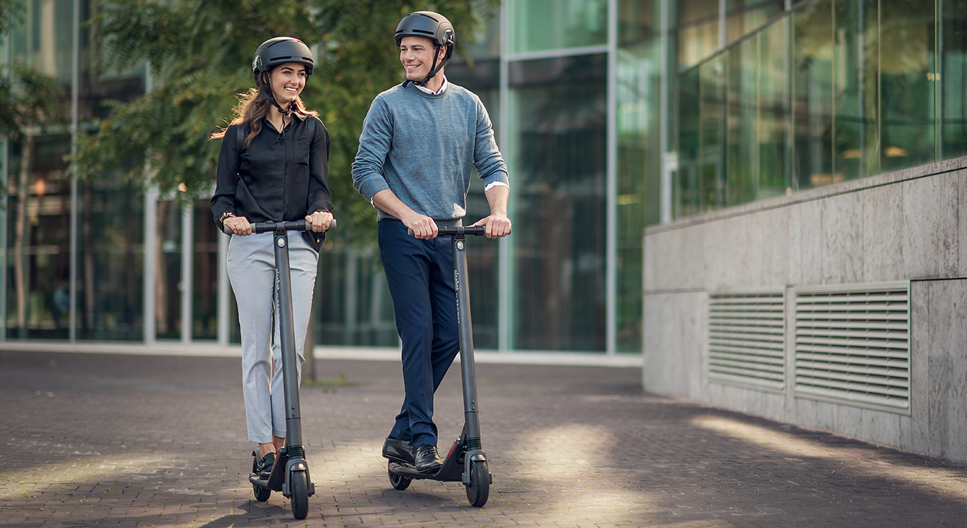Man and Woman in urban environment riding kickscooters