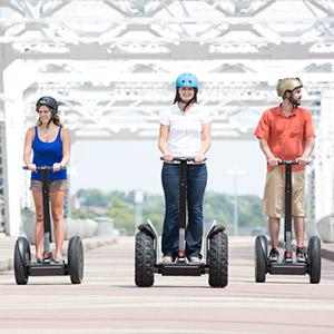 Three people on Segway PTs during tour on bridge