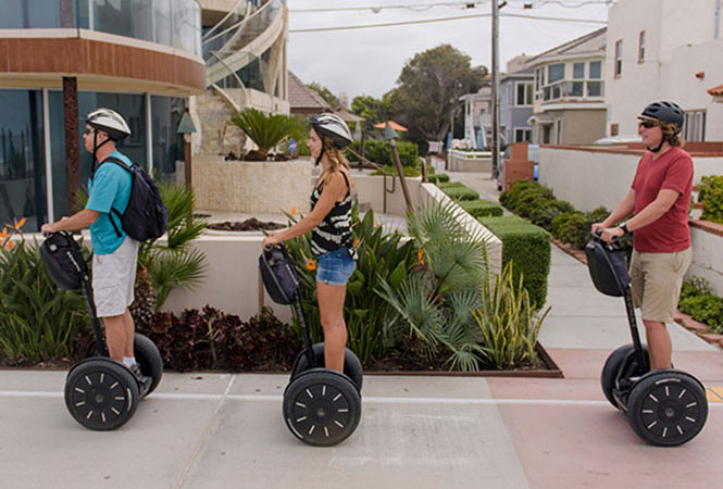 Tourists on Segway PTs as they travel down a street