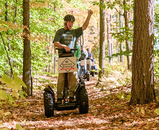 man on Segway tour in the woods with arm raised up
