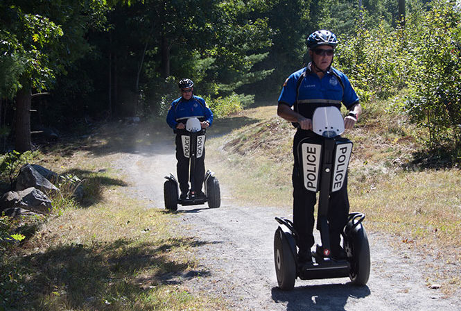 Two policemen riding Segway i2 se Patrollers on dirt path