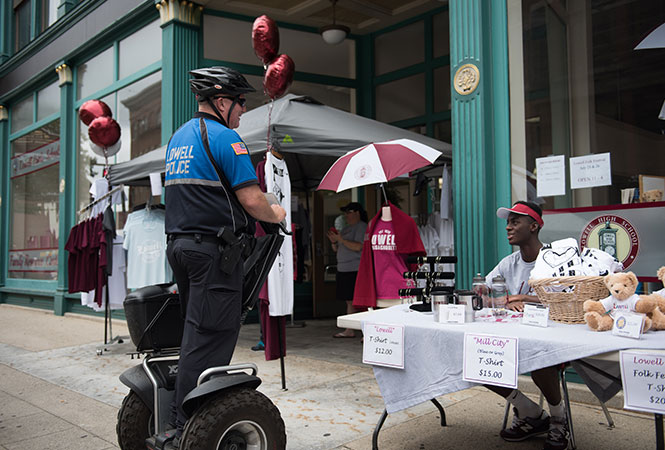Lowell, MA policeman using Segway x3 SE PT Patroller while talking with local merchant