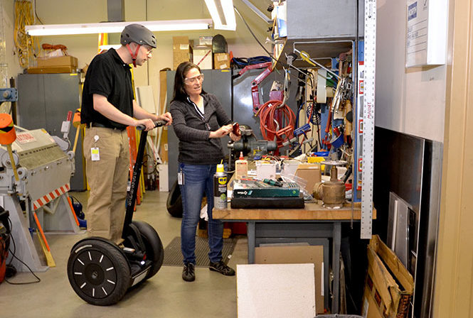 Foreman on Segway PT examing electrical component from female co-worker